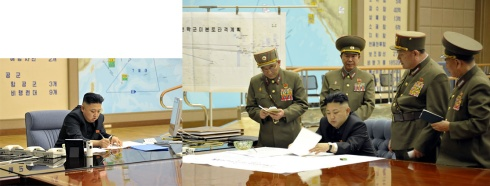 "Original March 29 KCNA official photo where Kim Jong-un signed off on the order at a midnight meeting of top generals to put its rocket units on standby to attack U.S. military bases and ""judged the time has come to settle accounts with the U.S. imperialists in view of the prevailing situation"", the official KCNA news agency said. Note map has no markings or translations"
