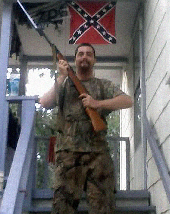 John Paul Cupp with SKS rifle in 2009 with confederate flag in the background. Photo taken in 2009 while he was advocating white supremacy and head of the official U.S. Songun Politics Study Group